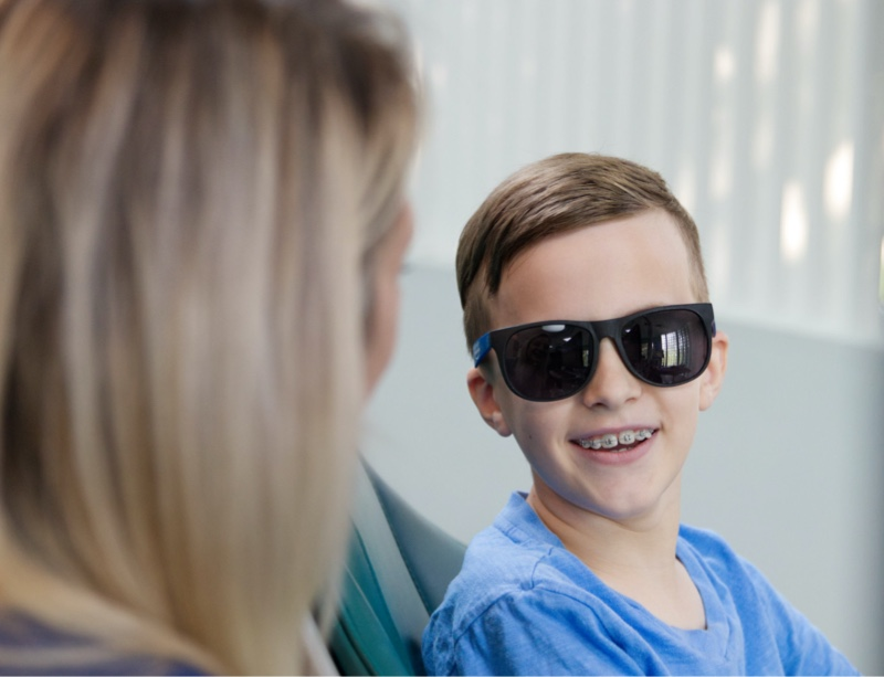 young patient smiling and wearing sunglasses